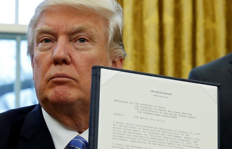 U.S. President Donald Trump holds up his executive order on the reinstatement of the Mexico City Policy after signing it in the Oval Office of the White House in Washington January 23, 2017.   REUTERS/Kevin Lamarque