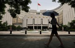 Una mujer pasa por delante de la sede del Banco Popular de China (PBOC), el banco central, en Pekín, China. 21 de junio 2013.  El banco central de China subió el martes las tasas de interés de una herramienta clave de financiamiento, el programa de créditos de mediano plazo (MLF), en su intento más reciente por controlar los niveles de deuda y reforzar la estabilidad financiera. REUTERS/Jason Lee/File Photo