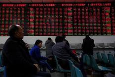 Инвесторы в брокерской конторе в Шанхае 3 января 2017 года. Китайские фондовые индексы снизились по итогам торгов пятницы, прервав пятидневную череду роста, после того как Пекин неожиданно повысил краткосрочные процентные ставки в первый торговый день после недельного перерыва на празднование Нового года по лунному календарю, вновь сигнализировав о намерении ужесточить политику. REUTERS/Aly Song