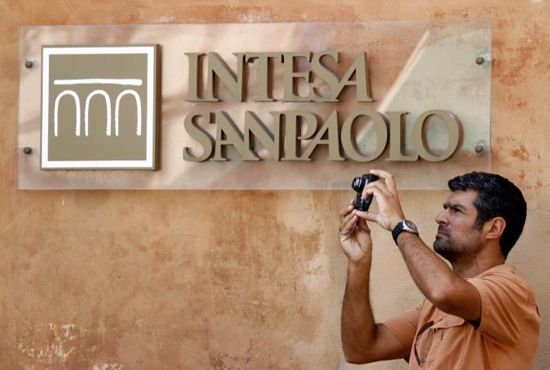 FILE PHOTO: A man takes a picture in front of Intesa Sanpaolo bank in downtown Rome, Italy, July 23, 2010. REUTERS/Alessandro Bianchi/File Photo