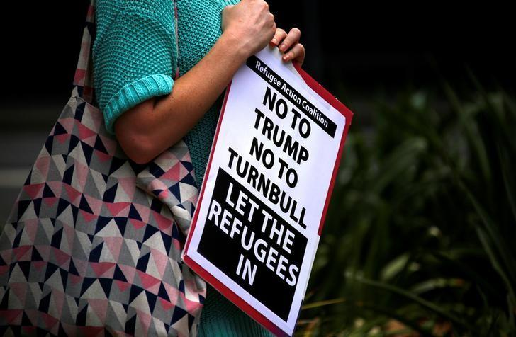 A protester holds a placard in Sydney, Australia, February 4, 2017 during one of several rallies across Australia condemning U.S. President Donald Trump's order temporarily barring refugees and nationals from seven countries and demanding an end to Australia's offshore detention of asylum seekers.    REUTERS/David Gray