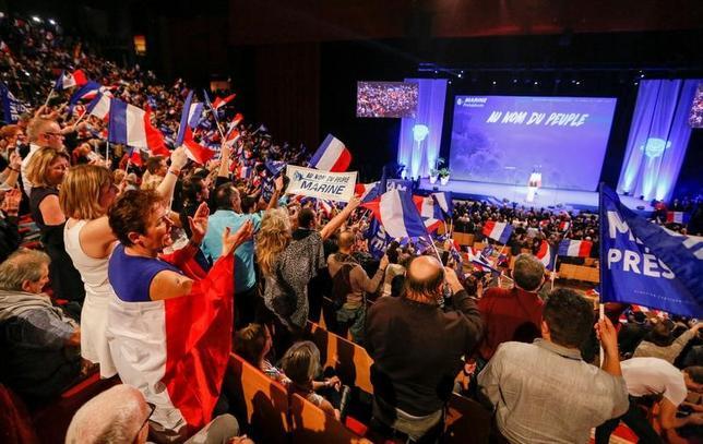 2月6日、仏大統領選は、家族への不正給与疑惑が浮上している中道右派、共和党のフィヨン元首相に対して出馬断念を求める声が高まるなど、選挙の行方は混沌としている。写真はリヨンでの大統領選運動の幕開けとなった国民戦線党の2日間にわたる選挙活動で、演説するルペン党首と支援者たち。5日撮影(2017年 ロイター/Robert Pratta)