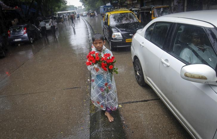 A boy sells roses while standing on a road divider during monsoon rains in Mumbai July 12, 2013. REUTERS/Danish Siddiqui/Files