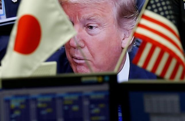 2月6日、日本はアメリカの経済敵国ではない。とはいえ、トランプ大統領が日本は円安誘導していると不満を口にしたわずか数日後、訪米を控えた安倍晋三首相は同大統領をなだめるため、大規模な米国への投資と雇用創出パッケージを用意している、と関係筋はロイターに語っている。写真は、テレビ画面に映るトランプ大統領と日米国旗。都内の為替トレーディングルームで1日撮影(2017年 ロイター/Kim Kyung-Hoon)