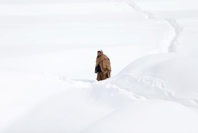 An Afghan man walks in a snow-covered street on the outskirts of Kabul, Afghanistan February 6, 2017. REUTERS/Mohammad Ismail