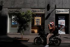 Un motociclista pasa frente a una casa de cambio de una sucursal del banco Mifel en Ciudad de México.Una posible subida de tasas de interés en México y las señales de mayor compromiso político en Brasil brindarían soporte a las cotizaciones del peso y del real esta semana, por más que la tendencia general continúa presentándose desafiante para las principales monedas de América Latina. REUTERS/Carlos Jasso