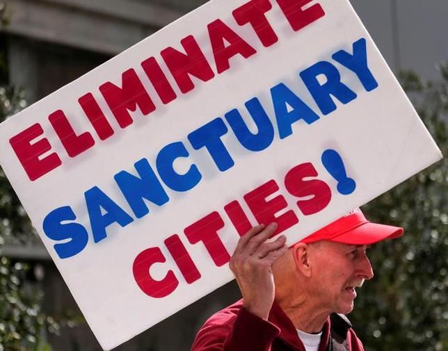 2月7日、イスラム圏7カ国からの入国を制限する米大統領令を巡り行われたサンフランシスコ連邦控訴裁判所の口頭弁論で、政権側の弁護士は、大統領令の一時差し止めを命じた連邦地裁の判断は誤りだと主張した。写真はトランプ政権の移民制限支持のカードを捧げる市民。カリフォルニア州ロサンゼルスで4日撮影(2017年 ロイター/Ringo Chiu)