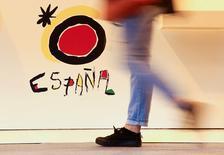 """El sindicato Comisiones Obreras (CCOO) instó el miércoles al Gobierno español a promover un pacto por el turismo para defender uno de los motores de la economía del país, diciendo que los récords del sector van acompañados de una """"explotación laboral"""" que calificó de """"cara B"""" del turismo español. En la imagen, una persona pasa junto a un logo de España en la Feria Internacional de Turismo (FITUR) el 18 de enero de 2017. REUTERS/Paul Hanna/File Photo"""