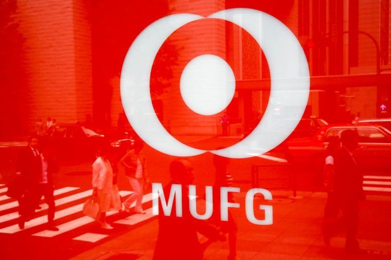 People are reflected in the logo of Mitsubishi UFJ  Financial Group's bank of Tokyo-Mitsubishi UFJ (MUFG) in Tokyo, Japan, May 16, 2016. REUTERS/Thomas Peter/File Photo