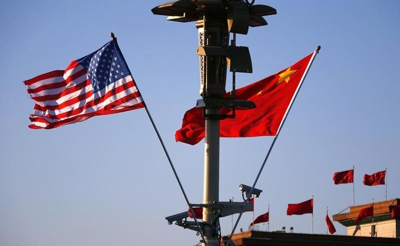 File Photo: U.S. (L) and Chinese national flags flutter on a light post at the Tiananmen Square ahead of a welcoming ceremony for then U.S. President Barack Obama, in Beijing, November 12, 2014. REUTERS/Petar Kujundzic