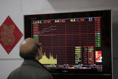 Инвестор наблюдает за графиками акций в брокерском доме в Шанхае. Основные фондовые индексы Китая повысились в пятницу и продемонстрировали максимальный недельный рост за более чем два месяца, возглавляемые акциями инфраструктурных и сырьевых компаний.  REUTERS/Aly Song
