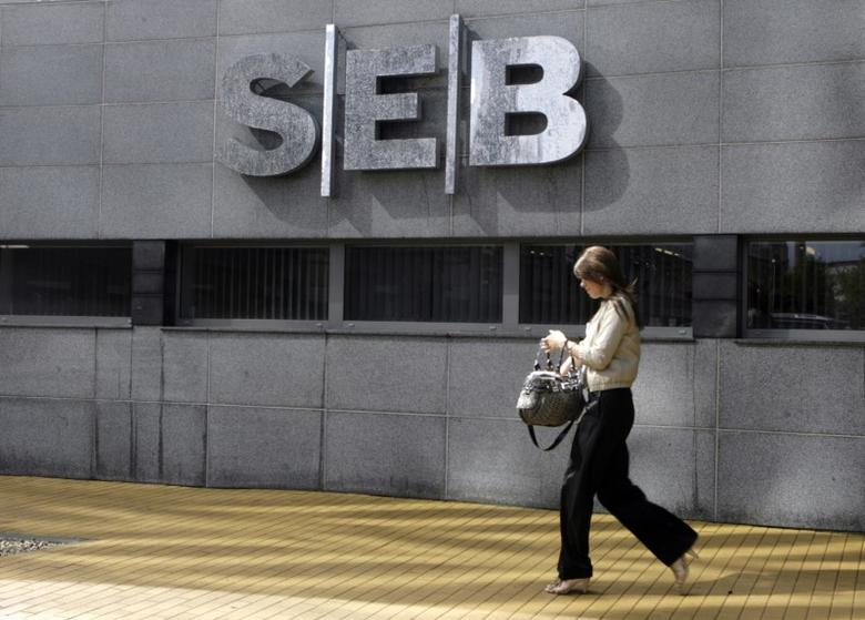 A woman walks past a SEB bank sign at the main office of the bank in Riga July 9, 2009. REUTERS/Ints Kalnins