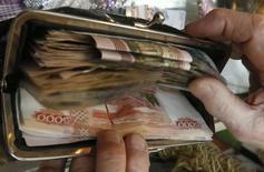 Кошелек с деньгами у покупательницы в Красноярске. Федеральный бюджет России в январе 2017 года был исполнен с дефицитом 23,4 миллиарда рублей, или 0,4 процента ВВП, сообщил Минфин.  REUTERS/Ilya Naymushin