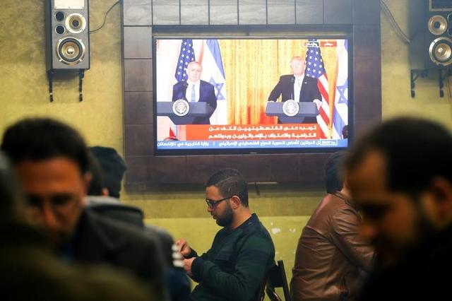 Palestinians play cards as a TV screen shows a joint press conference by U.S. President Donald Trump and Israeli Prime Minister Benjamin Netanyahu, in a coffee shop in the West Bank city of Hebron February 15, 2017. REUTERS/Mussa Qawasma
