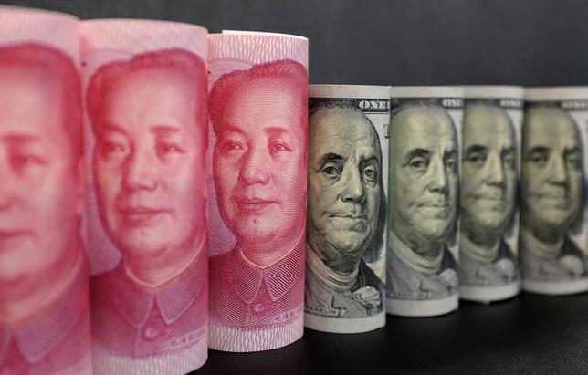 2月16日、中国商務省が発表した1月の金融を除く対外直接投資(ODI)は、前年比35.7%減の532億7000万元(77億7000万ドル)と16カ月ぶりの低水準となった。政府による資本流出規制で海外不動産投資が落ち込んだ。写真の人民元・米ドルは、北京で昨年1月撮影(2017年 ロイター/Jason Lee)