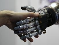 A man shakes hands with a humanoid robot during the International Conference on Humanoid Robots in Madrid November 19, 2014.  REUTERS/Andrea Comas