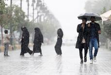 أناس يسيرون وسط الأمطار في الرياض يوم الخميس. تصوير: فيصل الناصر - رويترز