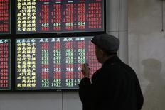 """Инвестор изучает информацию о торгах в брокерском доме в Шанхае. Китайский индекс """"голубых фишек"""" продемонстрировал в понедельник максимальный однодневный рост на последние шесть месяцев после сообщений СМИ о том, что средства пенсионных фондов могут начать поступать на фондовые рынки страны уже на этой неделе. REUTERS/Aly Song  (CHINA - Tags: BUSINESS)"""