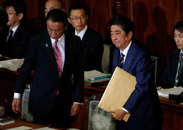 2月22日、麻生太郎副総理兼財務相(写真左)は財務金融委員会で、インフレによる政府債務解消を目指す「シムズ理論みたいなものがでてくると『いいじゃないか』と言う、いい加減な奴が出てくる」と批判し、あくまで歳出削減・歳入拡大による財政再建を進める重要性を強調した。写真は1月の通常国会で撮影(2017年 ロイター/Toru Hanai)