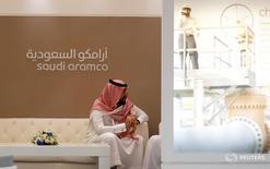 Сотрудник Saudi Aramcoсидит рядом со стендом компании на выставке Middle East Petrotech 2016. Нефтяной гигант Saudi Aramco попросил JPMorgan Chase & Co и Morgan Stanley помочь в проведении объемного IPO, а также может обратиться к другому банку с доступом к китайским инвесторам, сообщил источник, напрямую знакомый с ситуацией. REUTERS/Hamad I Mohammed - RTSPMKF