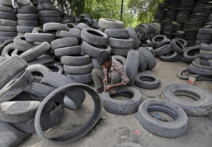 A man works at a tyre recycling unit on the outskirts of Ahmedabad, August 11, 2015. REUTERS/Amit Dave/Files