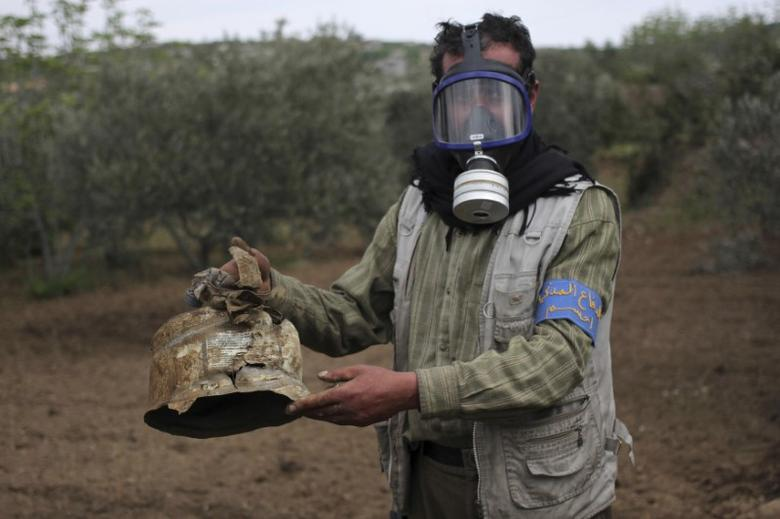 A Civil Defence member carries a damaged canister in Ibleen village from what activists said was a chlorine gas attack, on Kansafra, Ibleen and Josef villages, Idlib countryside, Syria May 3, 2015. REUTERS/Abed Kontar/File Photo