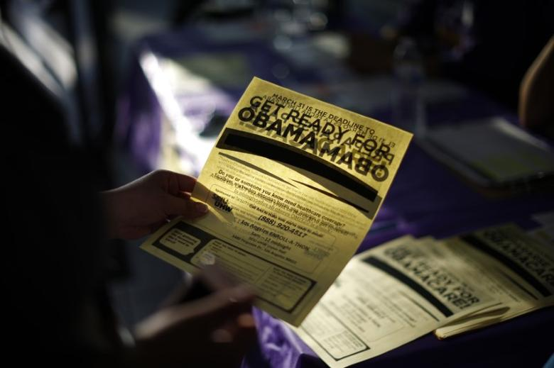 A woman picks up a leaflet at a health insurance enrollment event in Cudahy, California March 27, 2014. REUTERS/Lucy Nicholson