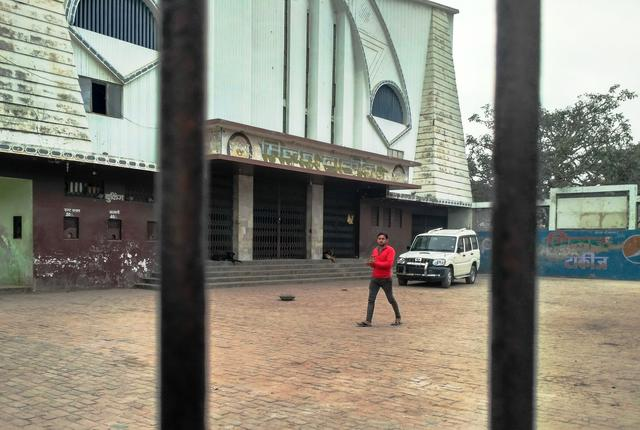 A man walks by as dogs guard the gates of Milan Talkies. Photo by Zeyad Khan