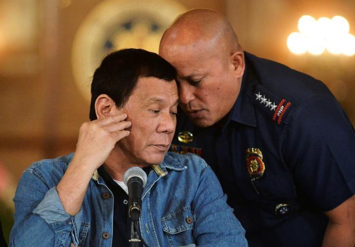 Philippine National Police chief General Ronald Dela Rosa whispers to President Rodrigo Duterte during the announcement of the disbandment of police operations against illegal drugs at the Malacanang palace in Manila, Philippines January 29, 2017. Picture taken January 29, 2017.       REUTERS/Ezra Acayan