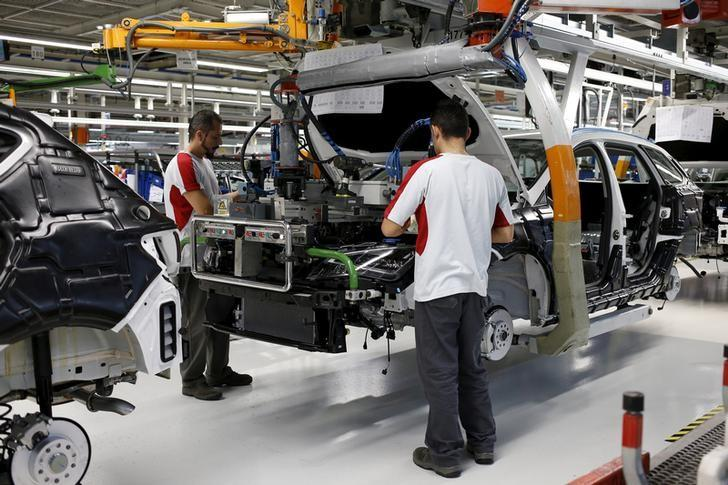 Workers from the SEAT factory, under the Volkswagen group, work on an engine of a SEAT Leon car, in Martorell near Barcelona December 5, 2014.  REUTERS/Gustau Nacarino/File Photo