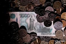 Рублевые монеты и банкнота 7 июня 2016 года. Рубль растет к евро и показывает минимальные изменения к доллару, отражая текущее снижение пары евро/доллар на форексе при плоской динамике нефти после её отскока с десятидневных минимумов, и на ближайшее время эти факторы останутся одними из основных для рубля после завершения налогового периода. REUTERS/Maxim Zmeyev/Illustration