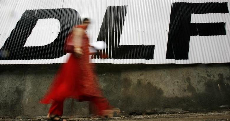 A woman walks past a billboard of Indian property developer DLF Ltd in Mumbai July 5, 2007.  REUTERS/Arko Datta (INDIA)