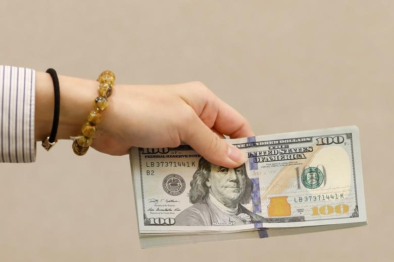 FILE PHOTO: A teller holds U.S. $100 dollar at a bank in Taipei, Taiwan February 23, 2017.  Picture taken February 23, 2017. REUTERS/Tyrone Siu/File Photo