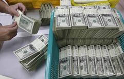 Работник отделения банка Kasikornbank считает деньги. Бангкок, 21 января 2010 года. Второй по величине госбанк ВТБ и банк Роснефти - Всероссийский банк развития регионов - в январе 2017 года зафиксировали приток валюты на корпоративные счета клиентов в объеме порядка $11 миллиардов, говорится в сообщении международного рейтингового агентства Fitch. REUTERS/Sukree Sukplang