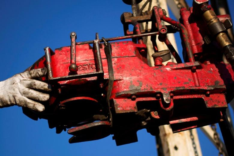 A man works on the rig of an oil drilling pump site in McKenzie County outside of Williston, North Dakota, U.S., March 12, 2013. REUTERS/Shannon Stapleton/File Photo