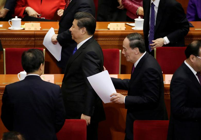 China's Politburo Standing Committee member Wang Qishan, the head of China's anti-corruption watchdog, talks to President Xi Jinping at the Great Hall of the People in Beijing, China, March 3, 2016. REUTERS/Jason Lee/File Photo
