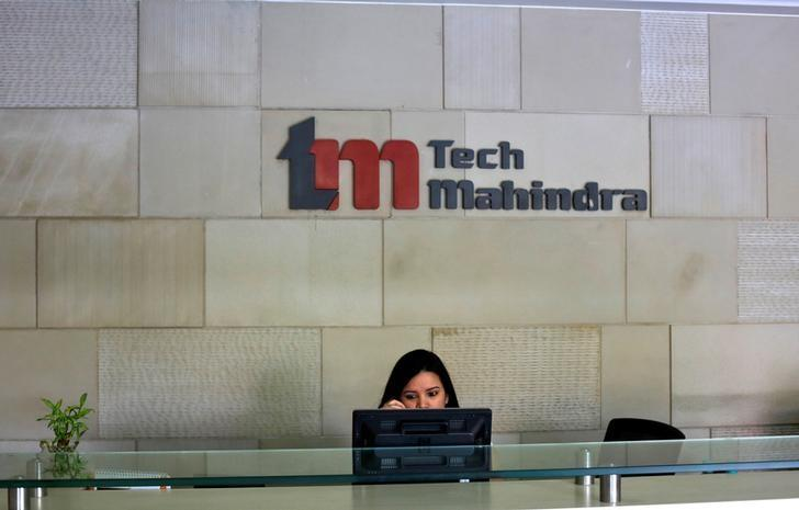 An employee sits at the front desk inside Tech Mahindra office building in Noida on the outskirts of New Delhi March 18, 2013. REUTERS/Adnan Abidi/Files