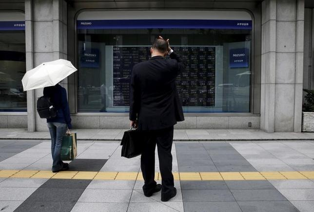3月7日、東京株式市場で日経平均は、3日続落。前日の米国株が反落し、小口の利益確定売りが先行した。売り一巡後はディフェンシブセクターの一角に買いが入り、4円安まで下げ渋る場面も見られたが、後場に為替がやや円高方向に振れると再び弱含みとなった。写真は都内の株価ボードを眺める男性。2015年8月撮影(2017年 ロイター/Toru Hanai)