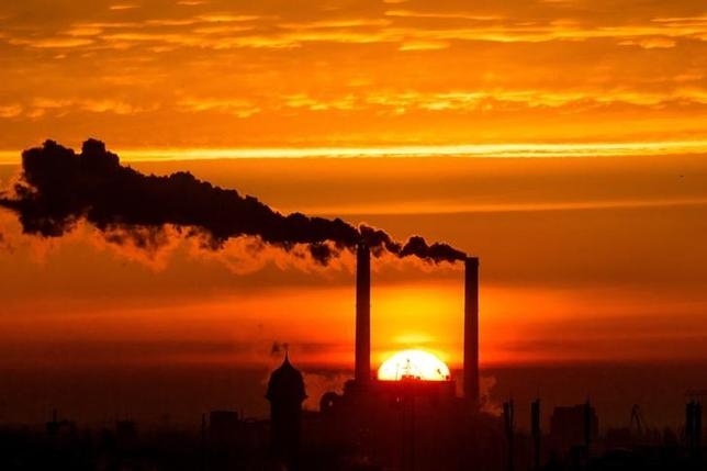 The sun rises behind the billowing chimneys of a power station in Berlin, Germany, November 27, 2013.   REUTERS/Thomas Peter/File Photo