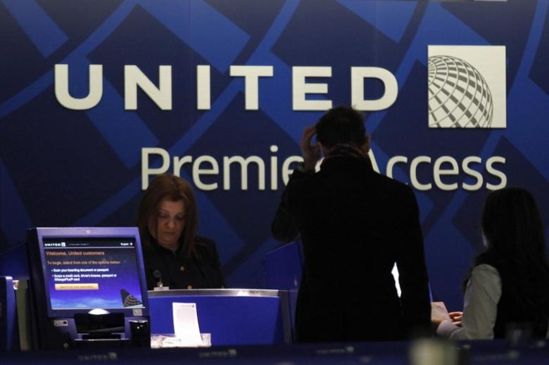 A worker from United attends to some customers during their check in process at Newark International airport in New Jersey , November 15, 2012. REUTERS/Eduardo Munoz