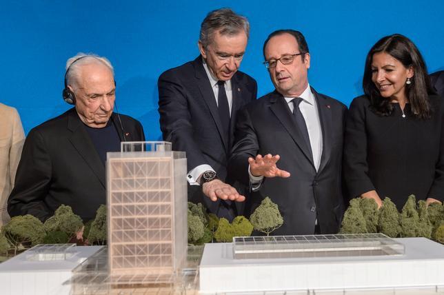 3月8日、フランス高級ブランドLVMH(モエ・ヘネシー・ルイ・ヴィトン)は、パリ郊外のルイ・ヴィトン財団近くにある国立民族民芸博物館跡の建物の改修計画に参入する。ベルナール・アルノーCEO(左から2人目)が、オランド仏大統領、パリのアンヌ・イダルゴ市長(右)、建築家のフランク・ゲーリー氏(左)とともに記者会見で発表した。代表撮影(2017年 ロイター/Christophe Petit Tesson)