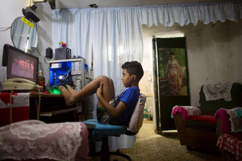 Kevin Lachaise, 8, watches a recorded TV show through the screen of a computer at the living room of his home in downtown Havana February 10, 2015. REUTERS/Alexandre Meneghini
