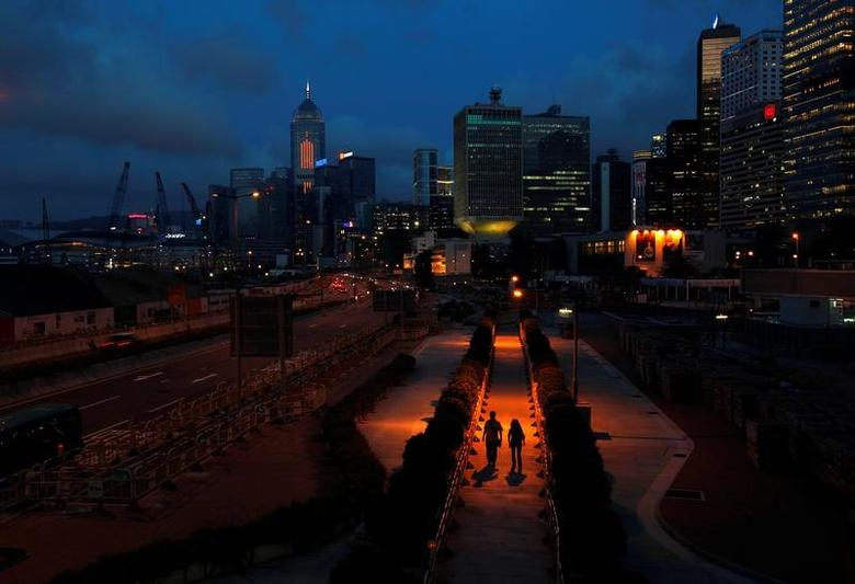 People walk on a pavement at Hong Kong's financial Central district during sunset May 11, 2011.   REUTERS/Bobby Yip/File Photo