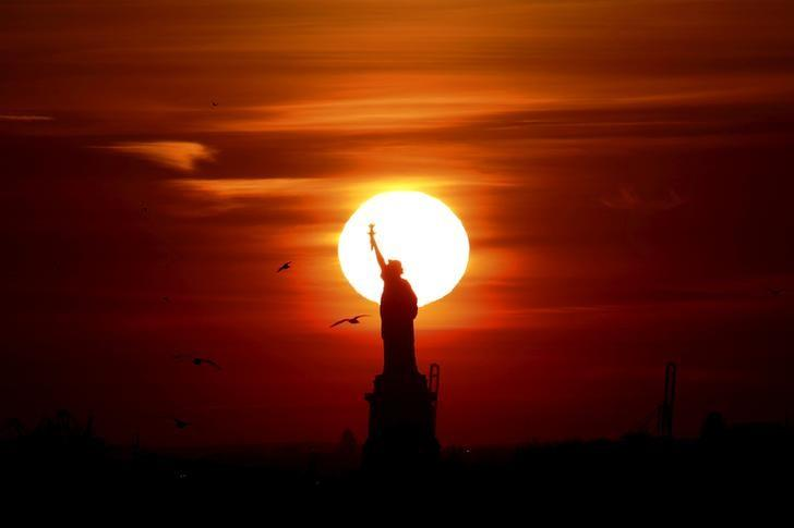 The sun sets behind the Statue of Liberty in New York's Harbor as seen from the Brooklyn borough of New York, USA February 27, 2016. REUTERS/Brendan McDermid/Files