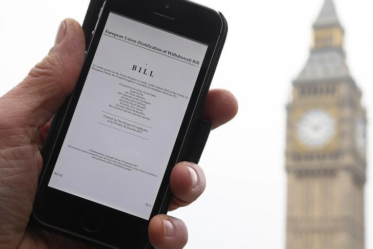 A man poses with an electronic copy of the Brexit Article 50  bill, introduced by the government to seek parliamentary approval to start the process of leaving the European Union, in front of the Houses of Parliament in London, Britain, January 26, 2017. REUTERS/Toby Melville