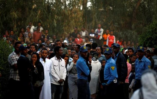 3月15日、エチオピアの首都アディスアベバの広報担当者は、同市のごみ集積所で起きた土砂崩れによる死者数が113人になったと明らかにした。うち75人は女性だという。写真はパワーショベルが集積れているゴミを掘り起こす様子を見守る市民(2017年 ロイター/Tiksa Negeri)