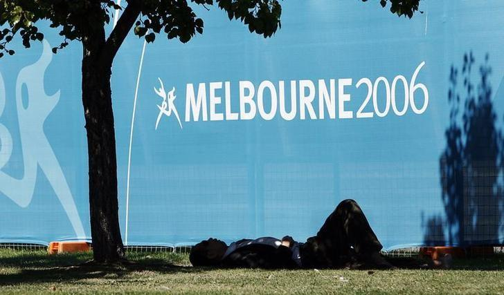A local resident sleeps in the shade of the hot afternoon sun outside the venue where weightlifting will be held at the Commonwealth Games in Melbourne, Australia March 12, 2006. The games get underway with opening ceremonies on March 15. REUTERS/Andy Clark/File Photo