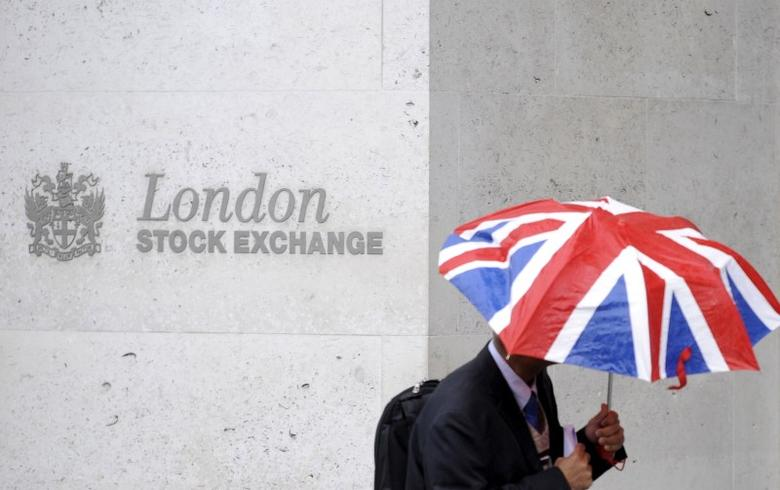 A worker shelters from the rain as he passes the London Stock Exchange in the City of London at lunchtime October 1, 2008.  REUTERS/Toby Melville/Files