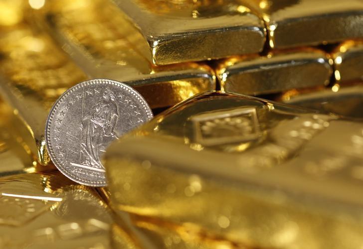 资料图片:2014年11月在维也纳拍摄的金条和一枚瑞士法郎硬币。REUTERS/Leonhard Foeger