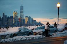 شخصان يزيحان الثلوج عن سيارتهما في نيوجيرزي يوم 14 مارس آذار 2017. تصوير: ادواردو مونوز - رويترز.